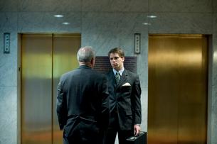 エレベータの前で立ち話をするビジネスマンの写真素材 [FYI03955379]