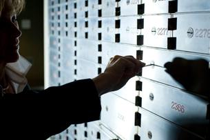 郵便受けの鍵を開けるビジネスマンの写真素材 [FYI03955385]