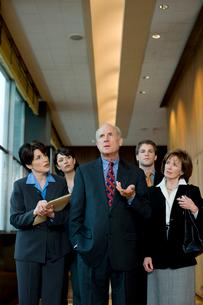 オフィスを歩くビジネスマンと傍を歩く男女の写真素材 [FYI03955392]