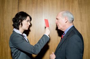 レッドカードを男性につきつけるビジネスウーマンの写真素材 [FYI03955400]