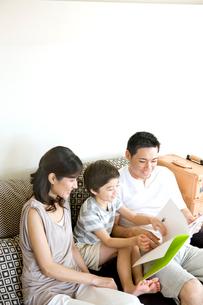 ソファで本を読む家族3人の写真素材 [FYI03955431]