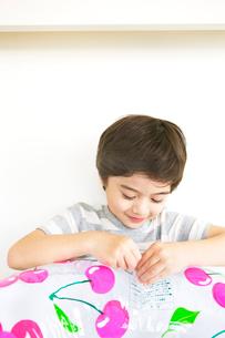 浮き輪をふくらませる少年の写真素材 [FYI03955432]
