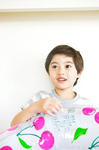 浮き輪をふくらませる少年の写真素材 [FYI03955433]