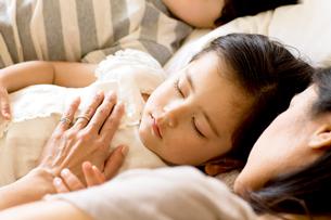 少女を寝かしつける母の写真素材 [FYI03955464]