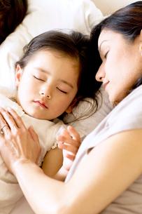 少女を寝かしつける母の写真素材 [FYI03955465]