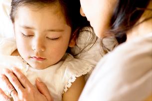 少女を寝かしつける母の写真素材 [FYI03955468]