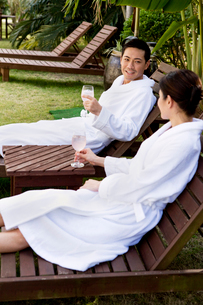 テラスの寝椅子でくつろぐ男性と女性の写真素材 [FYI03955473]