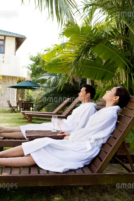 テラスの寝椅子でくつろぐ男性と女性の写真素材 [FYI03955476]