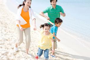 砂浜を走る家族4人の写真素材 [FYI03955503]