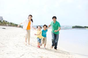 砂浜を走る家族4人の写真素材 [FYI03955506]
