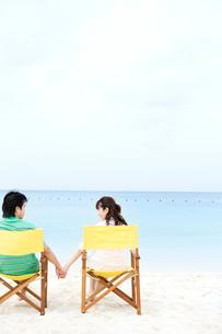 ビーチチェアに座る男性と女性の後ろ姿の写真素材 [FYI03955528]