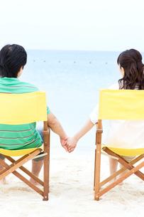 ビーチチェアに座る男性と女性の後ろ姿の写真素材 [FYI03955529]