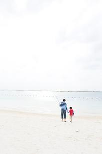 つり道具を持ち浜辺を歩く父と少年の写真素材 [FYI03955564]