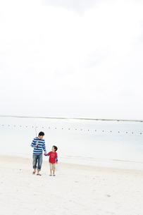 つり道具を持ち浜辺を歩く父と少年の写真素材 [FYI03955565]