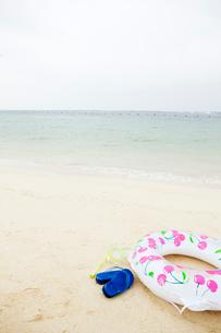 砂浜に置かれた浮き輪とビーチサンダルの写真素材 [FYI03955664]