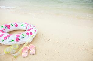 砂浜に置かれた浮き輪とビーチサンダルの写真素材 [FYI03955669]