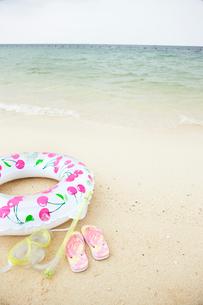 砂浜に置かれた浮き輪とビーチサンダルの写真素材 [FYI03955670]