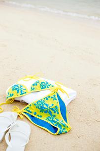 砂浜に置かれた水着とビーチサンダルの写真素材 [FYI03955675]