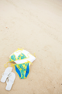 砂浜に置かれた水着とビーチサンダルの写真素材 [FYI03955678]