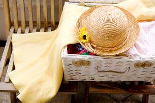 イスに置かれたカゴの旅行カバンと帽子の写真素材 [FYI03955698]