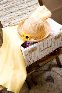 イスに置かれたカゴの旅行カバンと帽子の写真素材 [FYI03955700]