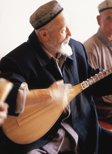 ドゥタールを弾くウイグル族の老人の写真素材 [FYI03957509]