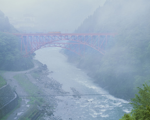 霧の山彦橋を渡る黒部渓谷鉄道の写真素材 [FYI03969554]