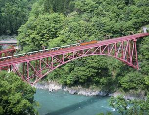 新緑の山彦橋を渡る黒部渓谷鉄道の写真素材 [FYI03969557]