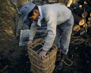 炭をわらで梱包する作業の写真素材 [FYI03977206]