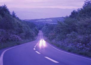 薄暮の道とヘッドライトの写真素材 [FYI03994773]