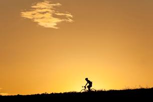 暮れ行く河川敷を行くサイクリストの写真素材 [FYI03995035]