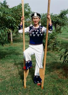竹馬とハニ族の女性の写真素材 [FYI04000270]