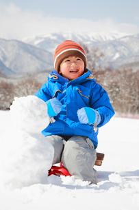 そりに乗って雪だるまを作る子供の写真素材 [FYI04018470]