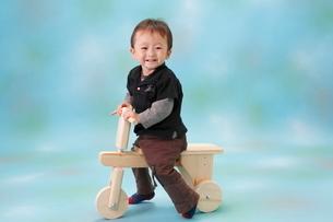 木の三輪車に乗って笑う男の子の写真素材 [FYI04018494]