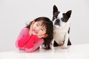 ほおづえをついて笑う女の子と犬の写真素材 [FYI04018500]