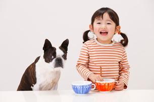 犬と一緒に食事する女の子の写真素材 [FYI04018501]