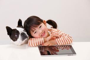 タブレットを触る女の子と犬の写真素材 [FYI04018503]