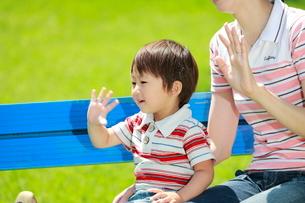 公園のベンチに座って手を振る男の子の写真素材 [FYI04018505]