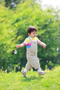 新緑の公園を走る男の子の写真素材 [FYI04018526]