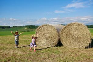 大きな干し草ロールの横を走る兄妹の写真素材 [FYI04018576]