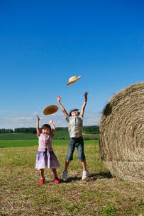 大きな干し草の横でジャンプする兄妹の写真素材 [FYI04018577]