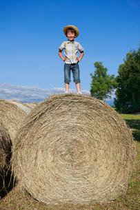 大きな干し草ロールの上に立つ男の子の写真素材 [FYI04018582]