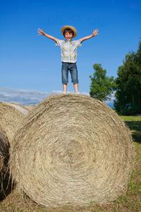 大きな干し草ロールの上に立つ男の子の写真素材 [FYI04018587]