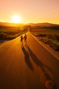 夕暮れの道を歩いて帰る兄妹の写真素材 [FYI04018589]