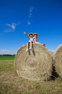 大きな干し草ロールの上の兄妹の写真素材 [FYI04018592]