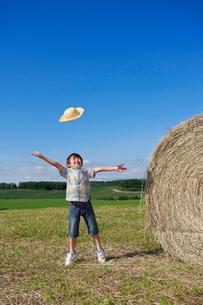 大きな干し草の横で麦わら帽子を投げる男の子の写真素材 [FYI04018593]