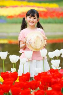 満開のチューリップと帽子を持った少女の写真素材 [FYI04018611]