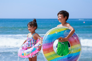 海で浮き輪を持った兄妹の写真素材 [FYI04018635]