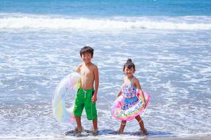 浮き輪を持って浜辺を歩く兄妹の写真素材 [FYI04018654]