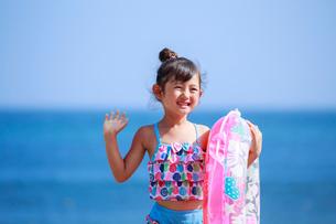 海で浮き輪を持って手をふる女の子の写真素材 [FYI04018655]